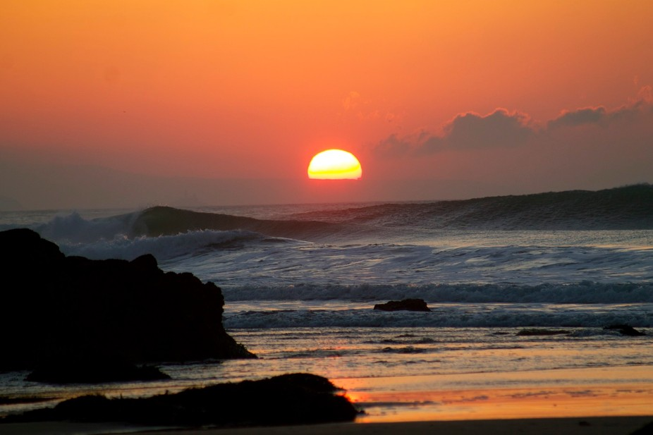 Sun setting behind the surf in Cornwall x.