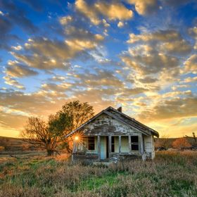 An abandoned home under South Dakota skies at sunset.