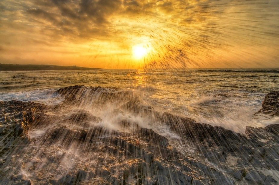 Sunrise on Inchadoney beach county Cork Ireland. The waves were crashing onto the rocks, which wa...