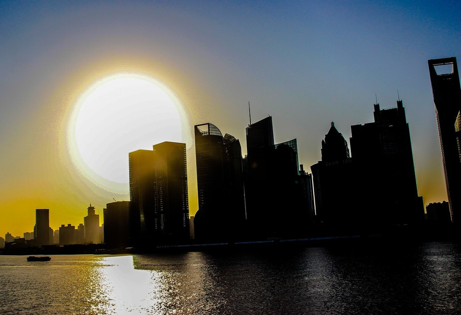 This large sun over the Shanghai , China at sunrise is a light source for this stunning silhouett...