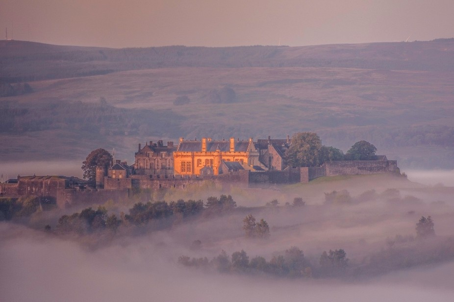 Stirling castle emerging from morning mist taken from the Wallace monument near Stirling, the sun...