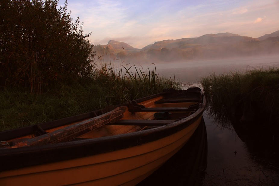 Boat on a small mountain lake in the west of Ireland. Early morning in autumn