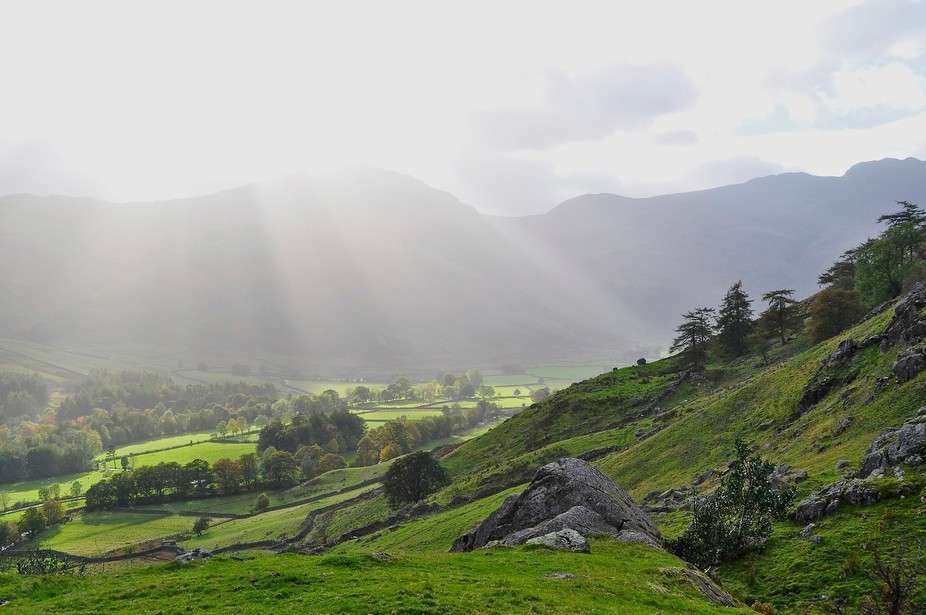 After a hard day's walk to the Langdale Pikes in Cumbria, England, our return to the valley from where we had started was a magical light display of vivid greens, dark clouds and piercing sunlight.