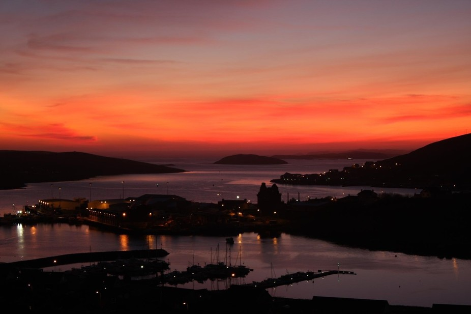 Sunset over the village and harbour of Scalloway , Shetland Isles with ancient castle in centre o...