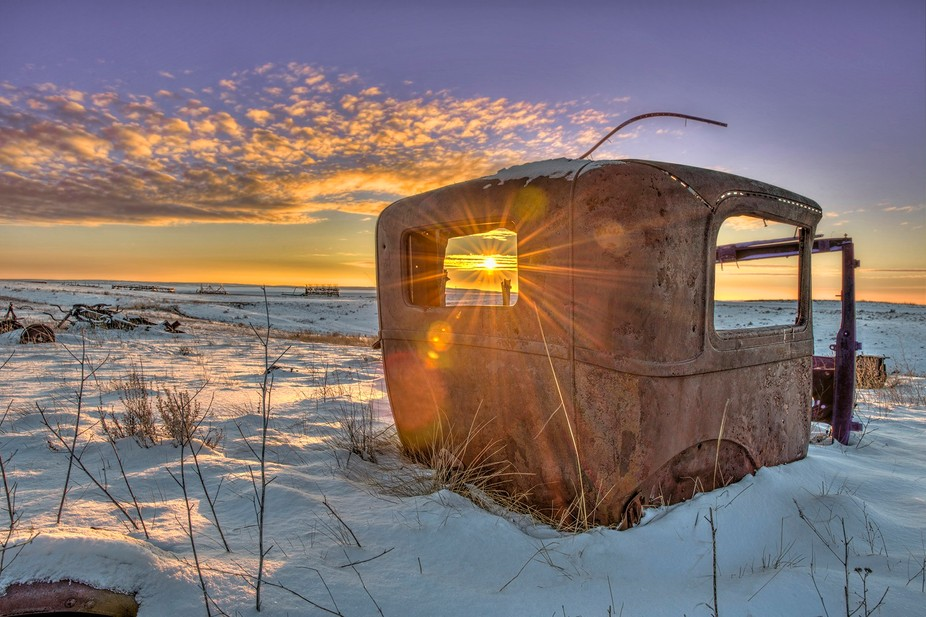 The setting sun through the window of an old rusty car on the winter prairies of saskatchewan can...