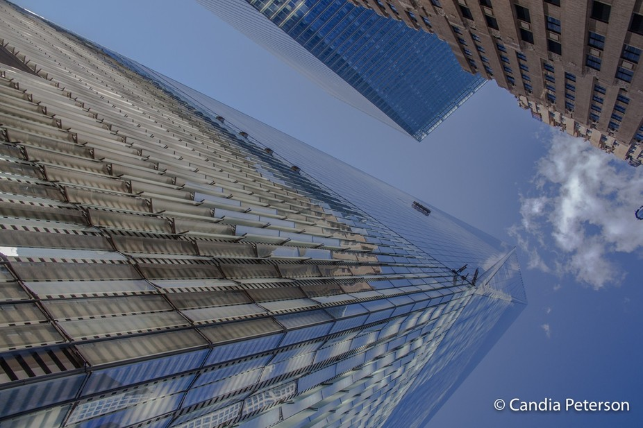 New York.  Looking up the Freedom Tower in New York with the blue sky and clouds plus buildings r...