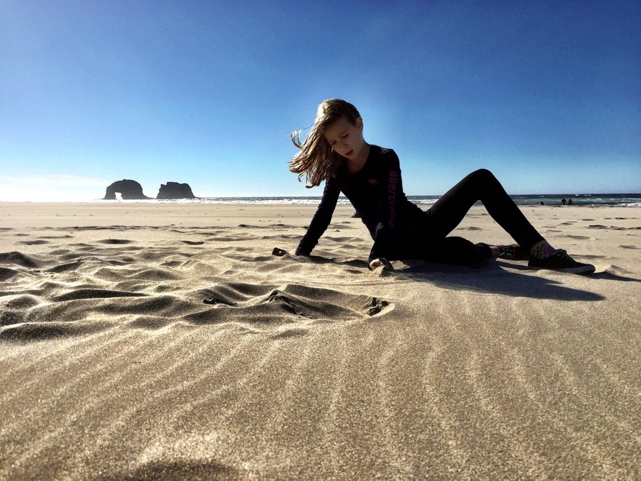 My 10 year old daughter soaking up the sun on an Oregon beach during a family road trip from Brit...