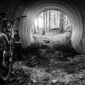 Photo taken and edited on my Google Nexus 5X phone. Mountain bike (Specialized Stumpjumper) leaning against a tree at the entrance to a tunnel on...