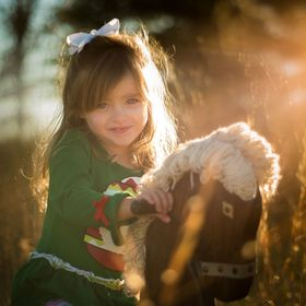 A little girl riding her wooden horse into the sunset.