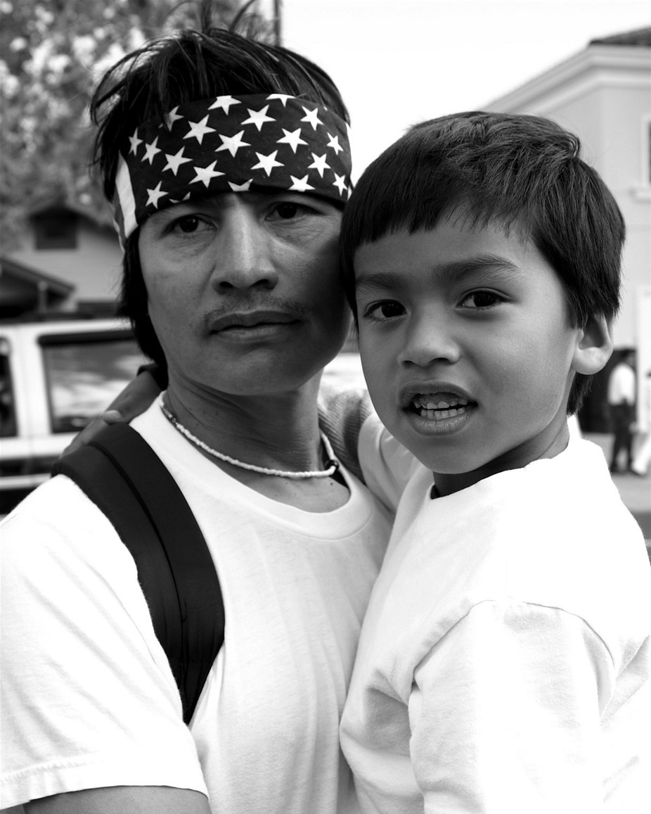B&W portrait of sad Latino blue collar worker and his son.