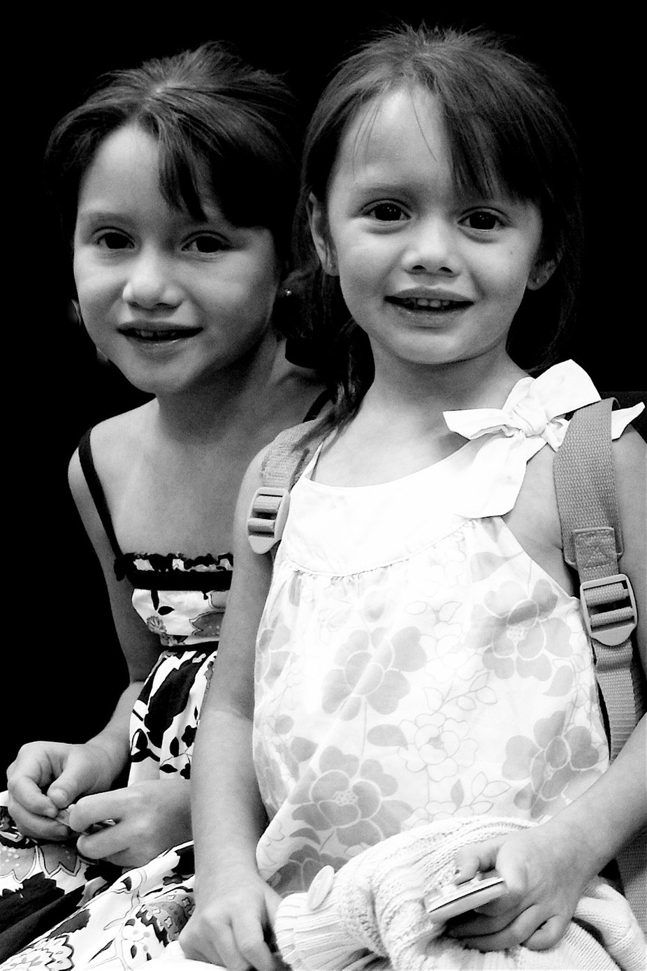 B&W of two little sisters with a shy smile.