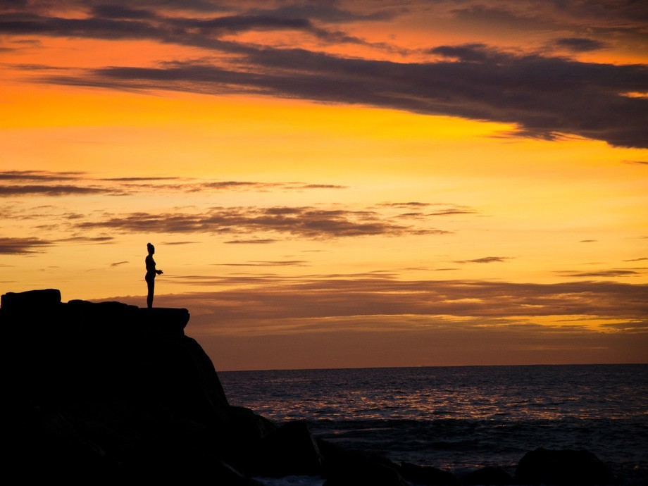 a solitary female figure peers over an outcrop of rocks along the shores of Mirissa, Sri Lanka, a...
