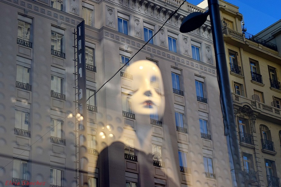 Shop window reflecting the buildings of Madrid's Gran Via