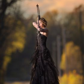 senior in a black prom dress with bow and arrow