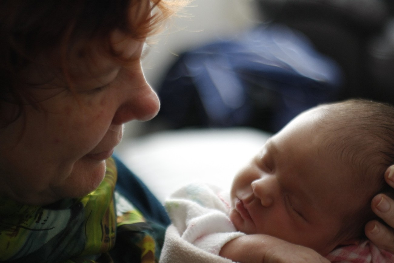 The joy of a grandmother holding a new grandchild for the first time.