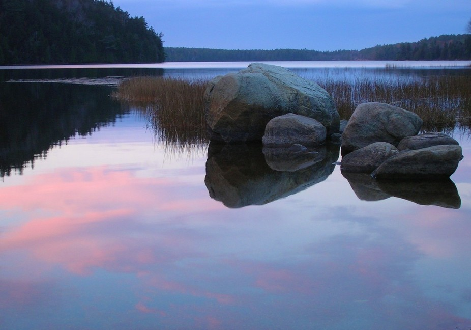 Fog nestles in the reeds behind boulders and reflections of a fall sunset on Echo Lake  Southwest...
