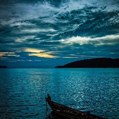 Man sits in bow of traditional fishing boat in Kota Kinabalu harbor, Sabah, Borneo, Malaysia.
