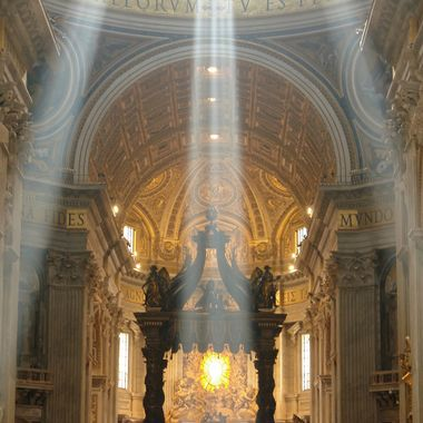 Three shafts of light dramatically illuminate the golden interior of St. Peter's Basilica while tourists mill about, oblivious to the spectacle.