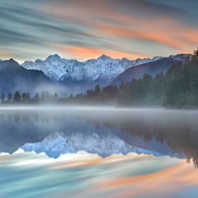 A beautiful calm morning on Lake Matheson on the South Island in New Zealand with Mt. Cook reflecting in the lake.