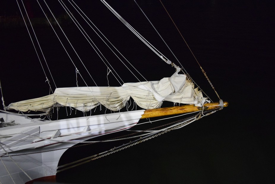 A picture of a sailing ship taken at night with the lighthouse lights shining down on it.