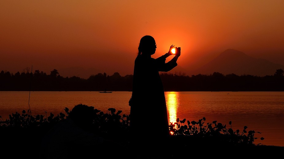 Sunset in finger tip: A pretty woman was trying to capture the beauty of sunset beside a lake by ...