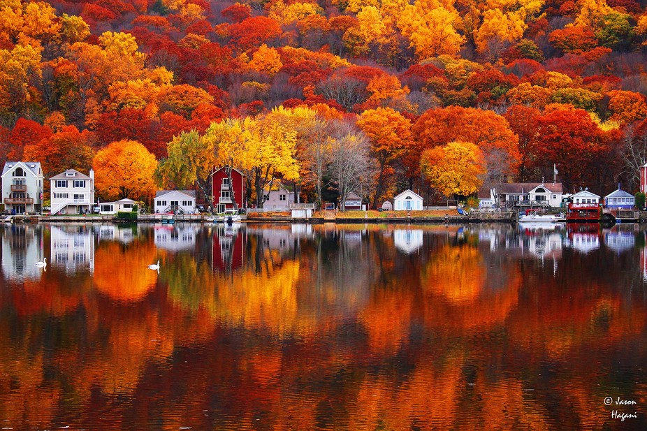 A small Connecticut town and the fall foliage behind it reflected into the clear Naugatuck River ...