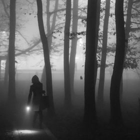 A girl looking like the little red hood walking in the forest in the fog lighting her way with a flash-light.