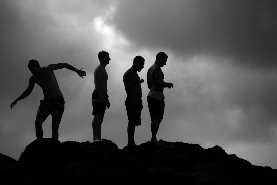 Youngsters anxiously waiting in line to dive the 35 feet from a lava rock into the pacific waters...