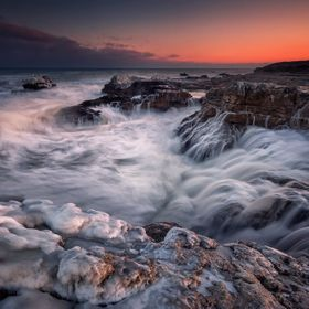 Fiery sunset and stormy waves near the frozen coast of the Black Sea, Bulgaria