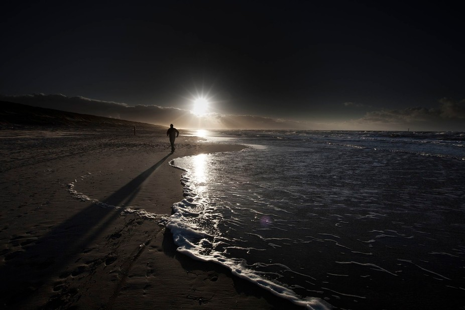 December light on Texel, sunset, jogger with long shadow