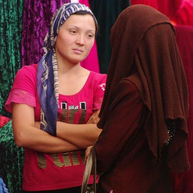 People were selling many different goods in a large market place in Kashgar, southwestern China. This woman was selling many colors of cloth, and was talking with another woman.