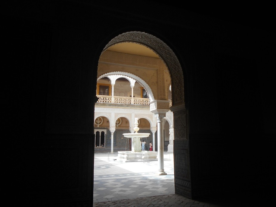Andalusian patio in Seville at midday, through an archway.