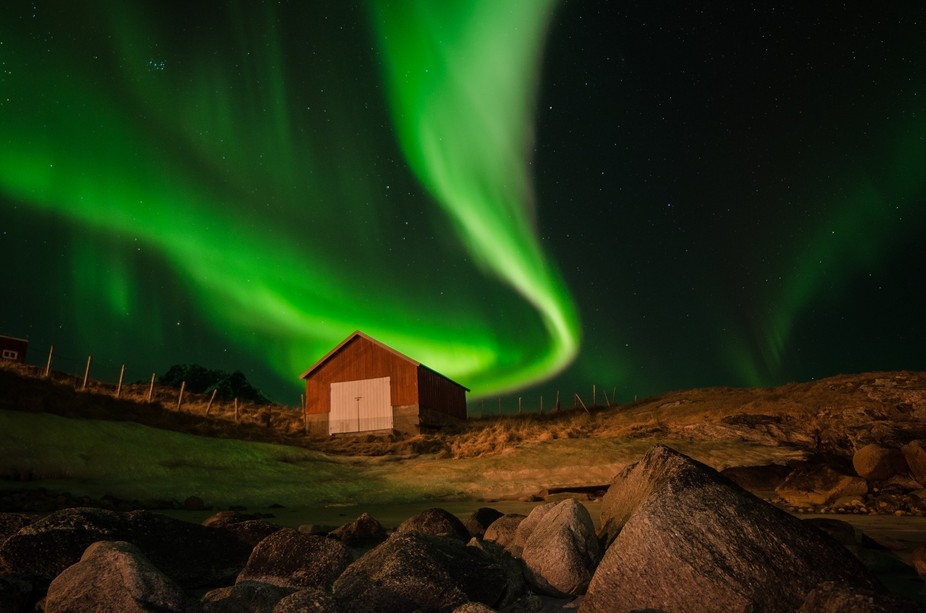 During a clear night, at the beach of Grøtfjord in Northern Norway, a beautiful aurora lights up...