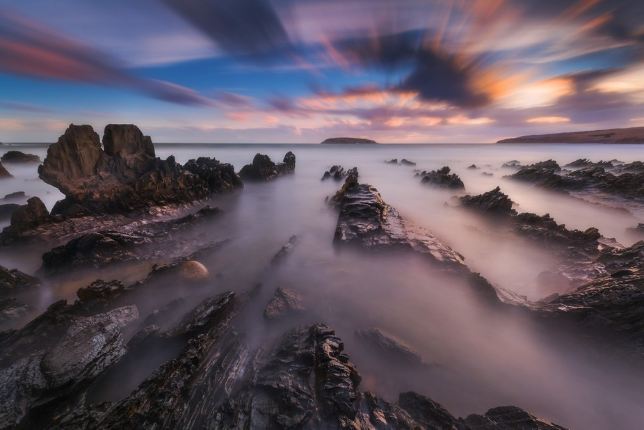 High clouds and low clouds move along their separate paths at Petrel Cove during a long exposure