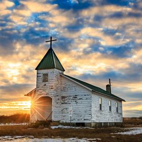 The setting sun peeks around the side of a little country church in rural South Dakota.