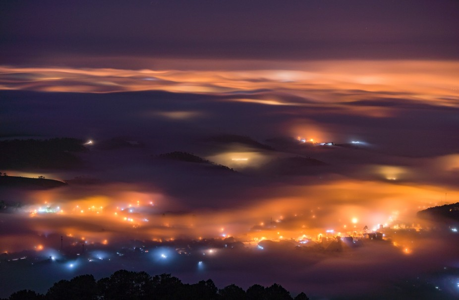 The light of the town in a foggy night from a mountain peak.