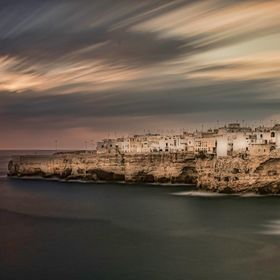 In the region of Pulgia, on the east coast of Italy, the town of Polignano a Mare sits perched on 30 metre high cliffs over the sea.