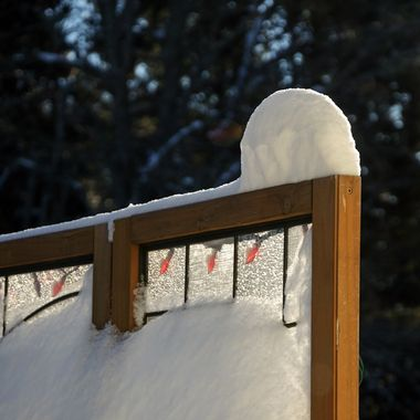 A snow covered wooden privacy screen with red Christmas lights.