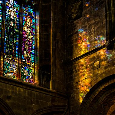 Sunshine shining through a stained glass masterpiece at Chester Cathedral and washing the wall with colour ..