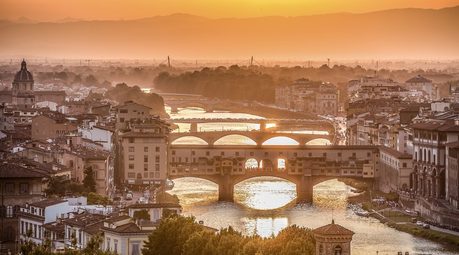 The Ponte Vecchio and the Arno River in the glowing summer sunset light