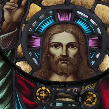 A closeup of of a depiction of Jesus on a stained glass window with elevated arm and holding chalice (unseen).