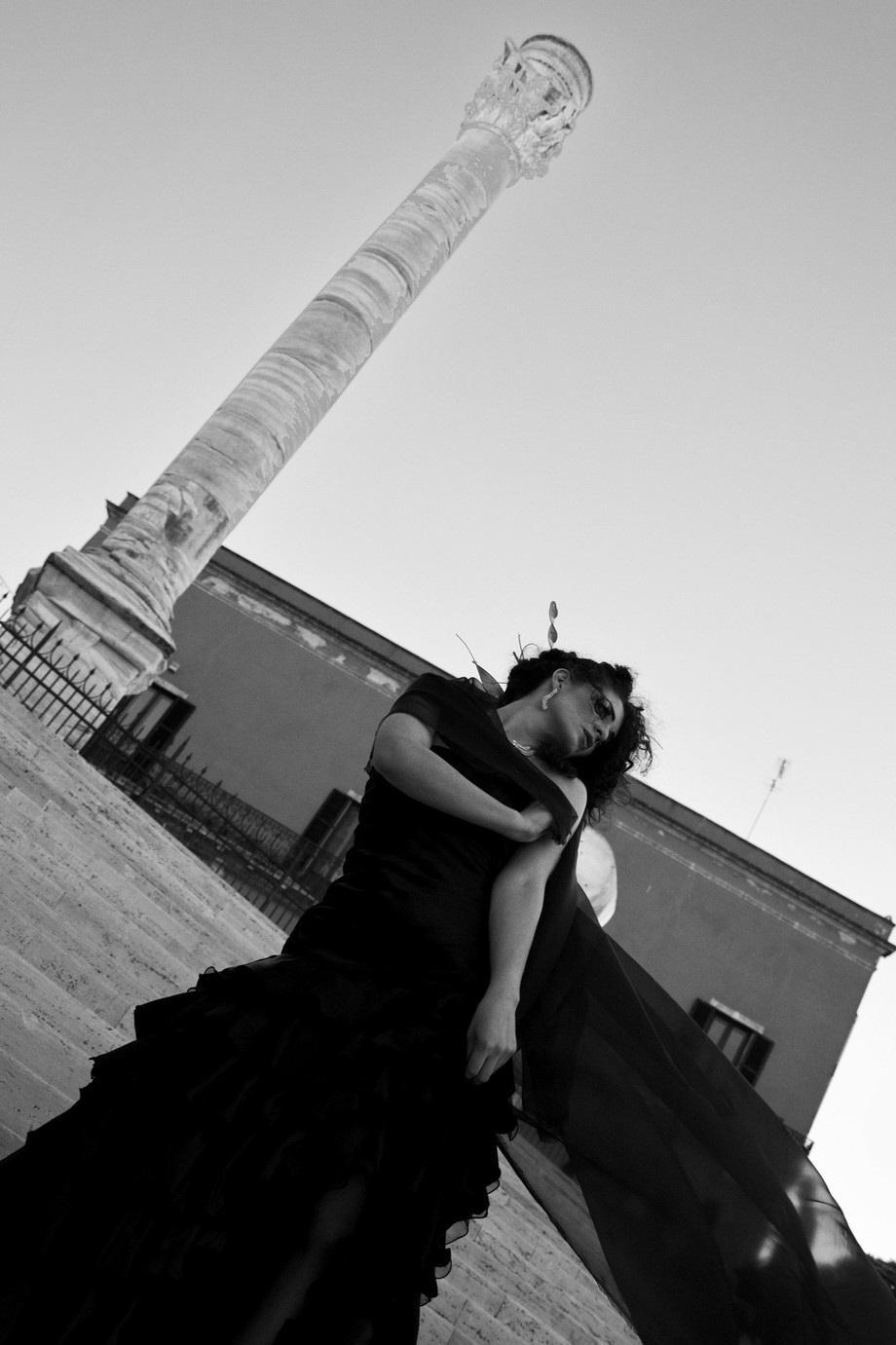 A shot made on the historic flight of steps where Virgil died. A young woman plays with her black dress, throwing it to the wind. Behind there are the Appia's columns