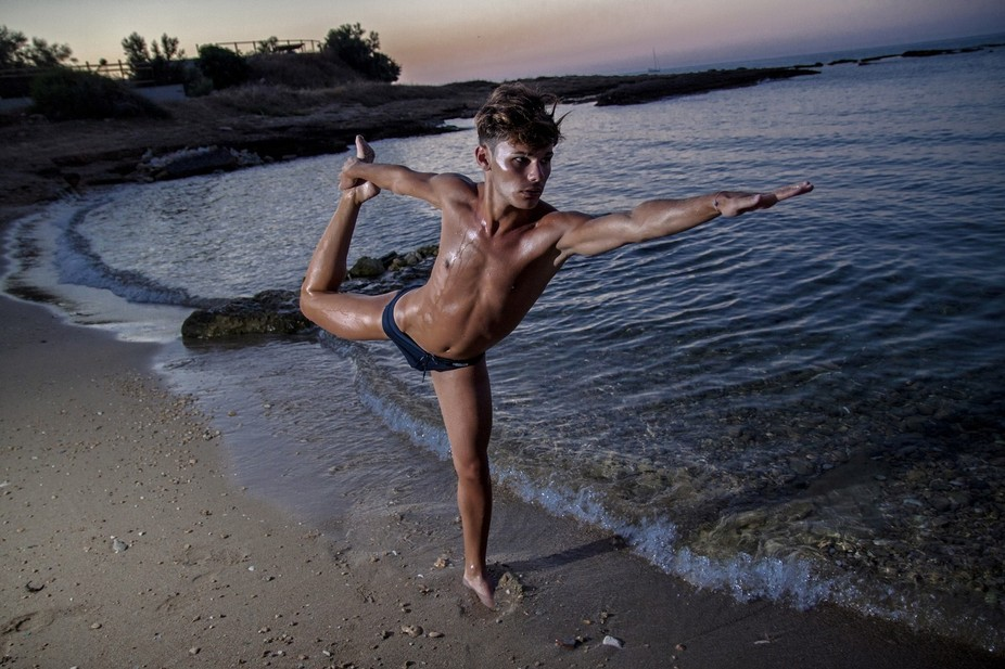 A young male is training in the shore, after the sun has set