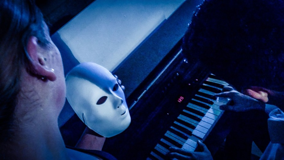 A creative shot made during a long night, with a smooth woman and a pianist. Then there is a white mask