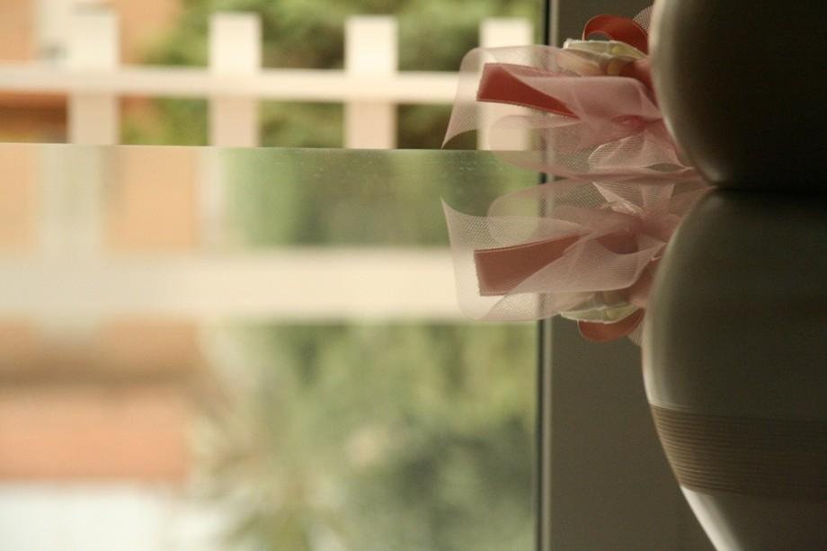 A table, a windows and a jar with a bow