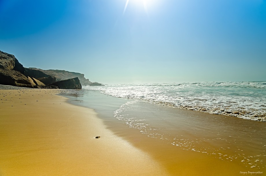 Beautiful oceanic beach with yellow sand and blue sky.