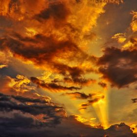 During golden hours before sunset, sun hide behind clouds. Sun rays coming from sun lit up some clouds in golden colour. The Cloud behind which s...