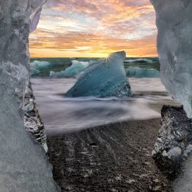 Watching the sun go down from a keyhole opening in an iceberg that had fractured off from  the glacier at Jokulsarlon lagoon and settled on the b...