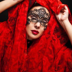 Model Christina Wilder lifting her red veil from her head with piercing gaze.