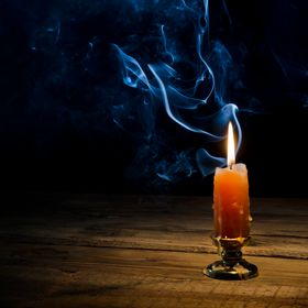 Burning candle and smoke on a dark background.